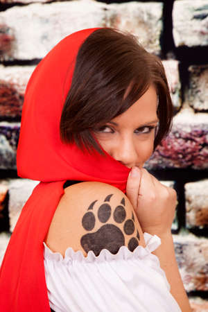 A woman hiding behing her red hood with her paw print on her arm showing. photo