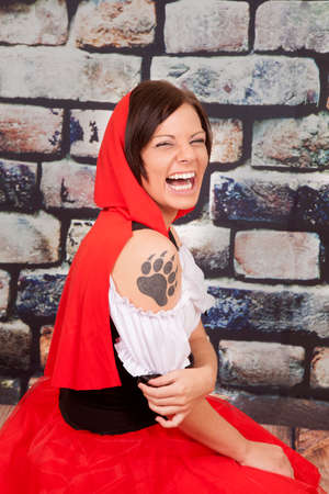 A woman laughing in her red hood and a wolf tattoo on her arm. photo