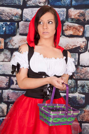 A woman in her red riding hood out fit holding a basket with a serious expression on her face. photo