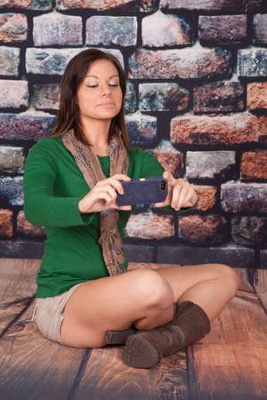 a woman sitting on a wood floor taking a picture of herself. photo