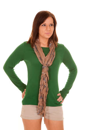 A woman with her hands on her hips with a scarf around her neck.