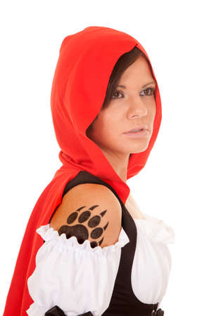 A woman in her red hood looking away with her paw print tattoo on her shoulder. photo