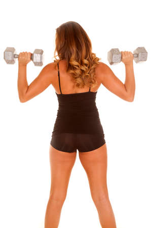 A woman working out with weights with her back to the camera. photo