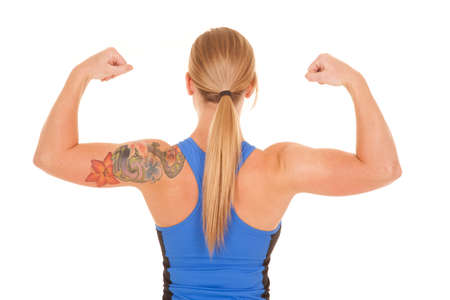 A woman looking forward flexing her muscles showing off her toned arms a d flower tatoo. photo