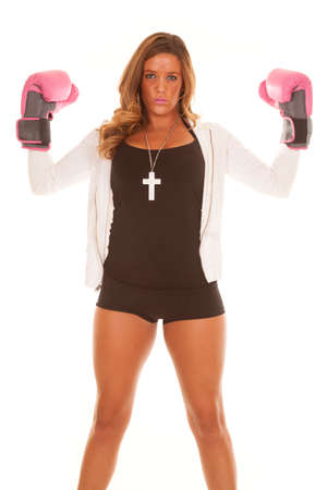 A woman with a serious expression on her face, flexing her arms with pink boxing gloves on. photo