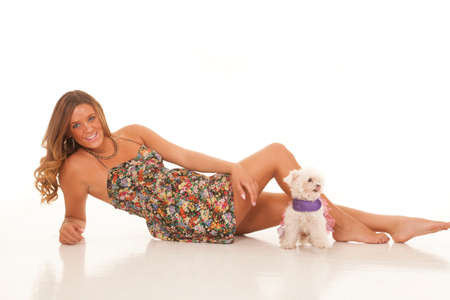 a woman laying back in her dress with her Maltese Poodle by her legs. photo