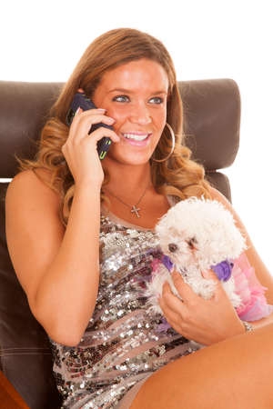 A woman sitting on the phone talking working and holding her puppy in her hand. photo