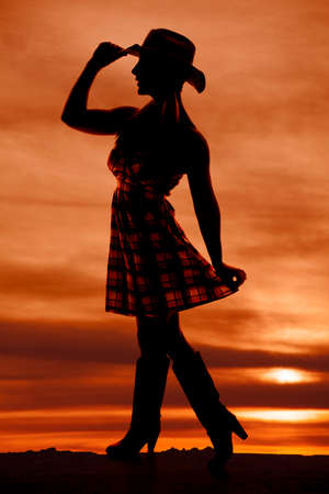 A silhouette of a woman standing holding out her checkered skirt and touching the brim of her cowgirl hat. Stock Photo - 23507250