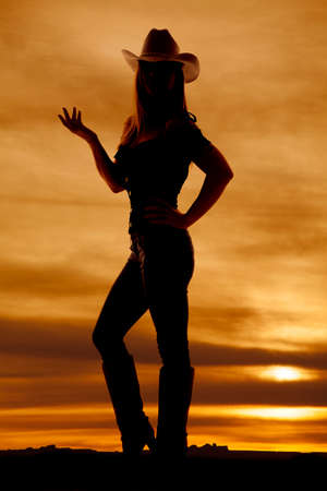 A silhouette of a woman in her jeans, boots, and hat standing in the outdoors with her hand up. Stock Photo - 23066653