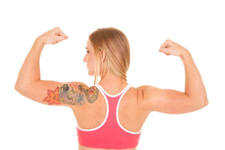 A woman flexing her arms with a back view with a tattoo. photo