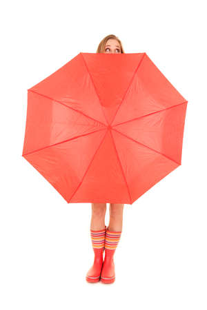 A woman in red rubber boots is holding a red umbrella. photo