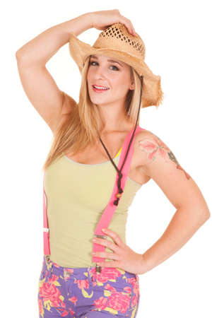A woman wearing pink suspenders is holding her cowboy hat. Stockfoto