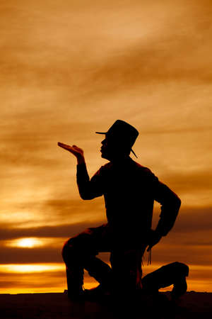 A silhouette of a cowboy on one knee blowing a kiss photo