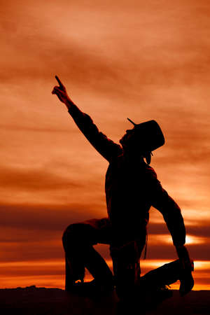 a silhouette of a cowboy reaching his arm up to the sky. photo
