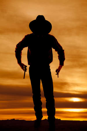 A silhouette of a cowboy holding onto his pistols. photo