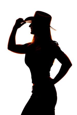 cowgirl hat: Una silueta de una mujer en su sombrero de vaquera aferrarse al ala del sombrero. Foto de archivo
