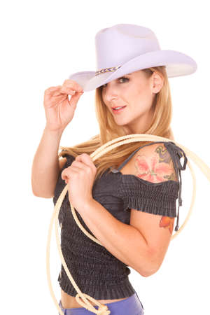 A woman in her purple cowgirl hat with a rope on her shoulder and a tattoo shoulder. photo