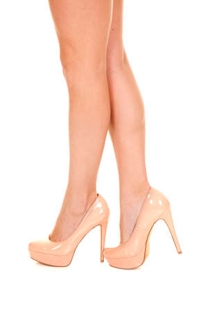 A side view of a womans legs in her cream heels. photo