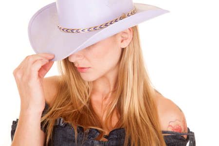 A close up of a womans face wearing a purple cowgirl hat with a serious expression. photo