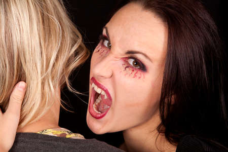 A female vampire getting ready to take a bite out of a womans neck. photo