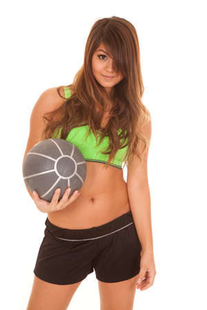 weighted: A Native American holding up her weighted medicine ball with a happy expression on her face.