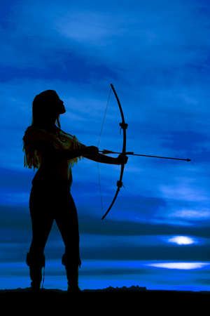 A silhouette of a Native American woman holding her bow getting ready to shoot her arrow. Stock Photo