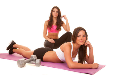 Two women are working out and one is layingon the floor. Stock Photo