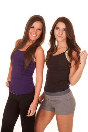 Two women are standing and smiling in fitness clothes. photo