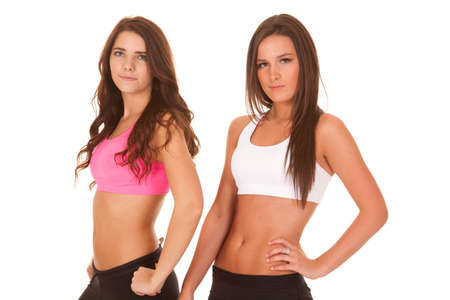Two women are standing in fitness clothes with serious expressions.