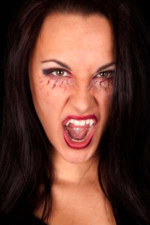 Een vrouw vampier pronken haar tanden met haar mond open.