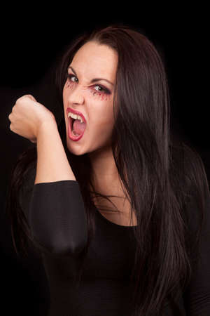 A female vampire getting ready to bite her own wrists. photo