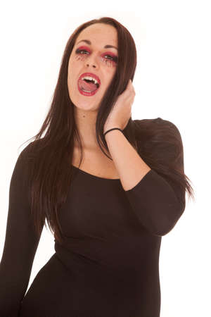 A female vampire with her mouth open and her tongue on her teeth. photo
