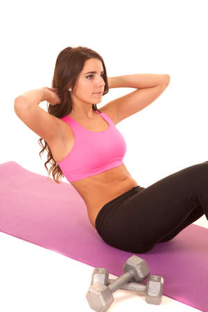 sit: A woman in a pink bra doing a sit up.