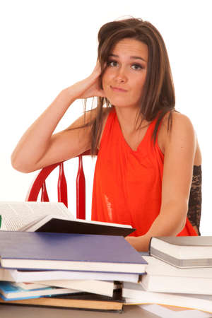 skeptic: A woman is sitting at a desk of books looking skeptical.
