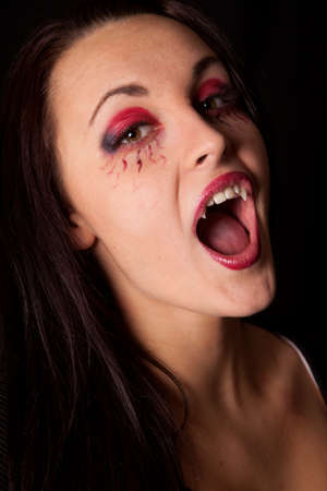 A close up of a vampire woman showing off her fangs photo