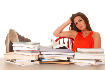 A woman in a red shirt studying books with a serious face. Stock Photo - 23507925