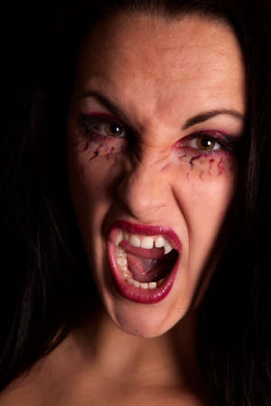 A female vampire  showing off her fangs. photo