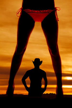 A silhouette of a womans legs in a bikini with a cowboy in the back. photo