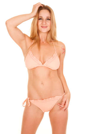 A woman in a peach colored bikini standing with a smile photo