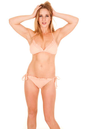 A woman in a peach colored bikini standing with her hands in her hair. photo