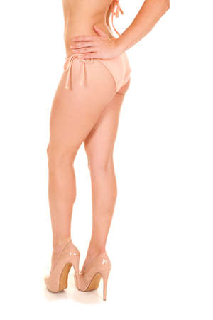 Legs of a woman in a peach colored bikini and heels photo