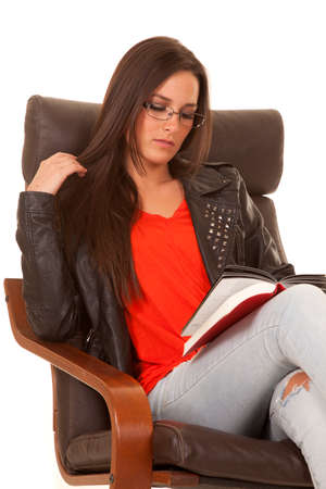 A woman is sitting and reading a book with a serious expression. photo