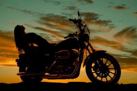 motorrad frau: Eine Silhouette einer Frau zur�ckgelehnt auf einem Motorrad.