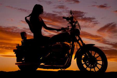 motorrad frau: Eine Silhouette einer Frau sitzt auf einem Motorrad. Lizenzfreie Bilder