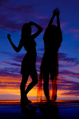 A silhouette of two women dancing together. photo