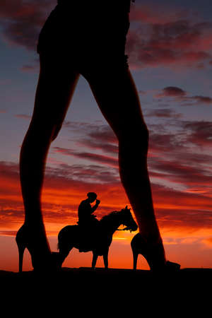 A silhouette of a womans legs facing sideways with a cowboy on a horse. photo