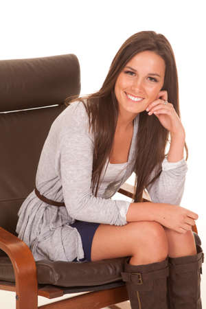 attractive young woman: A woman is sitting in a chair and smiling while leaning forward.