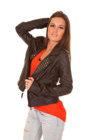 A woman is wearing a leather jacket with her hand up in her hair. photo