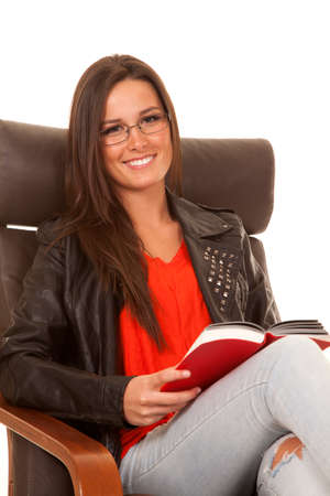 A woman is sitting in a chair and is smiling while holding a book. photo
