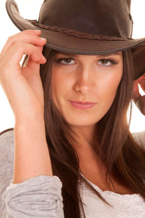 brim: A woman is holding the brim of her hat and smiling.
